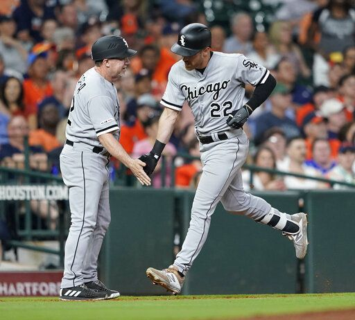 Chicago White Sox's Charlie Tilson (22) is congratulated by third base coach Nick Capra after hitting a grand slam against the Houston Astros during the sixth inning of a baseball game Wednesday, May 22, 2019, in Houston.