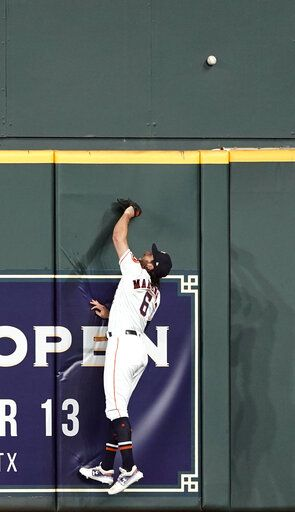 Houston Astros center fielder Jake Marisnick leaps at the wall while trying to catch a home run by Chicago White Sox's Eloy Jimenez during the second inning of a baseball game Wednesday, May 22, 2019, in Houston.