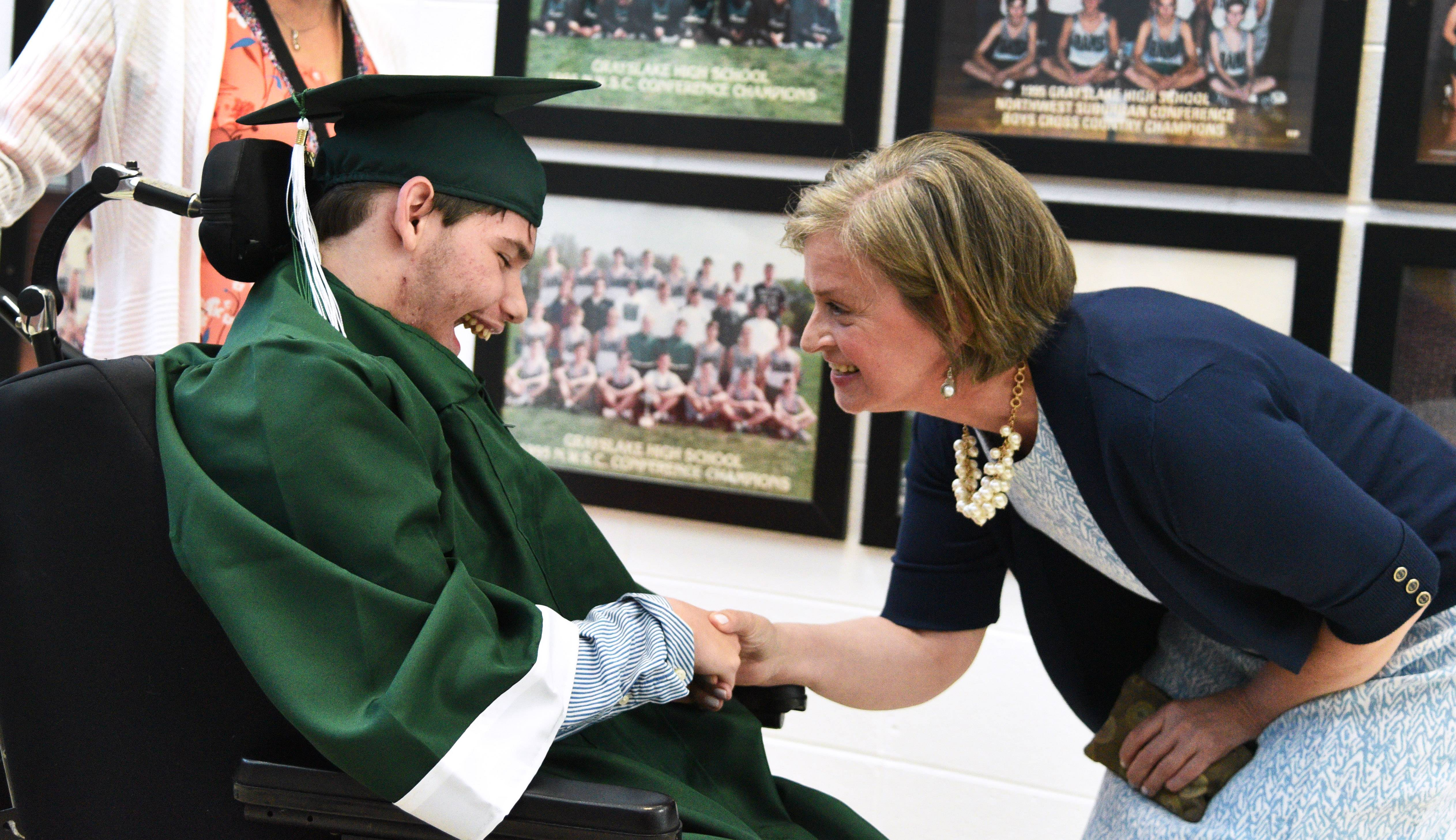 Grayslake District 127 school board President Kathleen Conlon-Wasik, right, congratulates Grayslake Central High School student Angelo Butler at the start of Thursday's graduation ceremony. Angelo completed four years of the Special Education District of Lake County (SEDOL) program at the school.