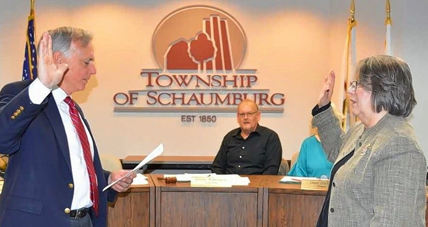 Char Kegarise, right, is sworn in as newly appointed Schaumburg Township trustee by Gary Seyring as Schaumburg Township Supervisor Timothy Heneghan looks on.