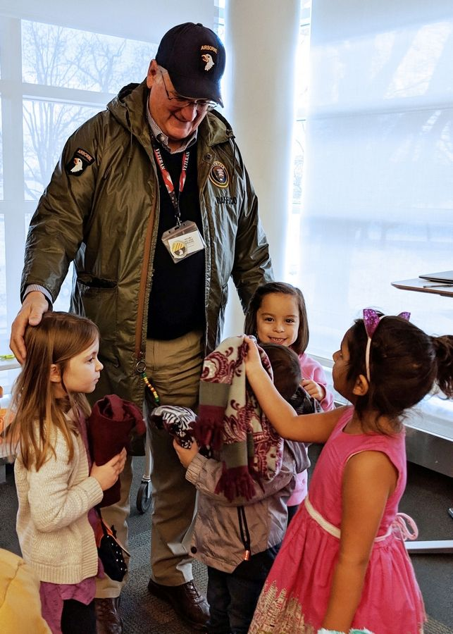 Paul Baffico, founder and president of the Lake County Veterans and Family Services Foundation, is greeted by young patrons at the Vernon Area Public Library in Lincolnshire during an event there.