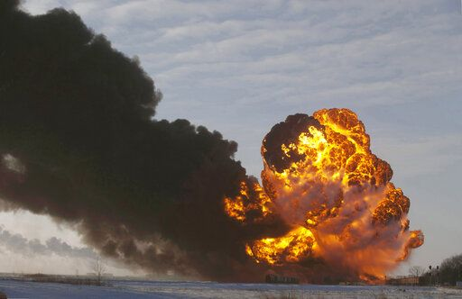 FILE - In this Dec. 30, 2013 file photo, a fireball goes up at the site of an oil train derailment near Casselton, N.D. The Trump administration is withdrawing a proposal for freight trains to have at least two crew members that was drafted in response to explosions of crude oil trains in the U.S. and Canada. Transportation officials said Thursday, May 23, 2019 that a review of accident data did not support the notion that having one crew member is less safe than a multi-person crew.