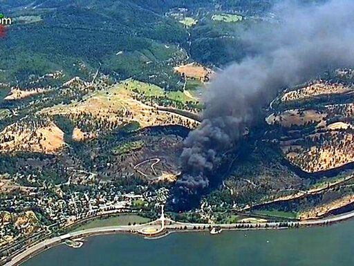 FILE - In this June 3, 2016 file image from video provided by KGW-TV, smoke billows from a Union Pacific train that derailed near Mosier, Ore., in the Columbia River Gorge. The Trump administration is withdrawing a proposal for freight trains to have at least two crew members that was drafted in response to explosions of crude oil trains in the U.S. and Canada. Transportation officials said Thursday, May 23, 2019 that a review of accident data did not support the notion that having one crew member is less safe than a multi-person crew. Forty-seven people were killed (KGW-TV via AP, File)