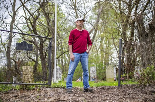 "In this Wednesday, May 1, 2019 photo, Jeff Purvis stands in front of his family's gravesite in southern Marion County, Ind. The land where the gravesite sits was settled by Purvis' great-great-great-grandfather, Alexander Joyce, in the late 1830s. When he settled, Joyce brought a slave, Price Joyce, with him from Patrick County, Virginia. The grave of Price was unmarked until Purvis placed a stone where he believes Price's body lays. ""I didn't enslave this man,"" said Purvis, wiping away tears. ""But I do have it in my power to apologize. And my God, I'm sorry. Too little, too late."" (Mykal McEldowney/The Indianapolis Star via AP)"
