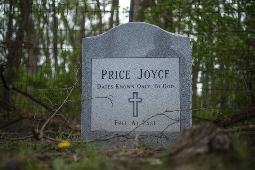 "In this Wednesday, May 1, 2019 photo, the grave of Price Joyce sits in a small, multi-family cemetery plot at Sampson Cemetery, in southern Marion county, Ind.  The grave of Joyce, a slave brought from Patrick County, Virginia to Indiana by Alexander Joyce in the 1830s, was unmarked until Joyce's great-great-great-grandson, Jeff Purvis, placed a head stone. ""I would like to believe the old family stories that he freed Price before leaving Virginia,"" said Purvis. ""But I see no compelling evidence to support that."" (Mykal McEldowney/The Indianapolis Star via AP)"