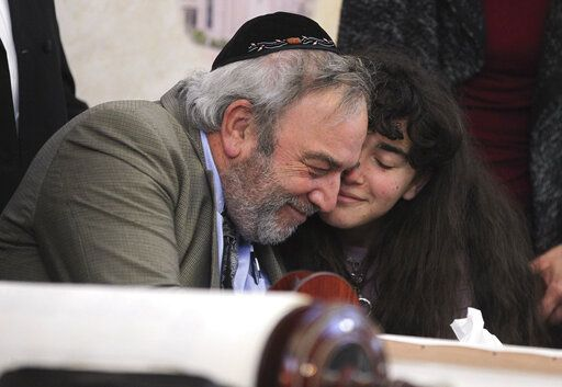 Howard Kaye, center, and his daughter Hannah Kaye, hug after the final letter was inked into the new Torah that's dedicated to wife and mother Lori Kaye, who was killed when a gunman attacked the Chabad of Poway in April, during a celebration for the new scroll at the synagogue, Wednesday, May 22, 2019, in Poway, Calif. (Hayne Palmour IV/The San Diego Union-Tribune via AP)