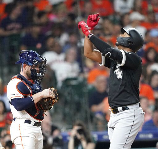 Chicago White Sox's Eloy Jimenez, right, celebrates after hitting a home run as Houston Astros catcher Max Stassi stands at home plate during the fourth inning of a baseball game Thursday, May 23, 2019, in Houston.