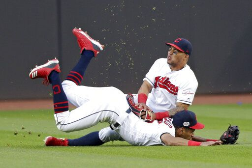 Cleveland Indians' Leonys Martin, top, and Oscar Mercado collide while going after a ball hit by Tampa Bay Rays' Kevin Kiermaier during the sixth inning of a baseball game Thursday, May 23, 2019, in Cleveland. Kiermaier hit a three-run home run.