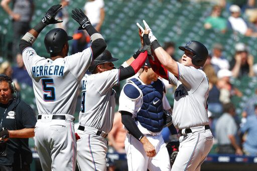 Miami Marlins' Garrett Cooper, right, celebrates with teammates after hitting a grand slam in the ninth inning of a baseball game against the Detroit Tigers in Detroit, Thursday, May 23, 2019.