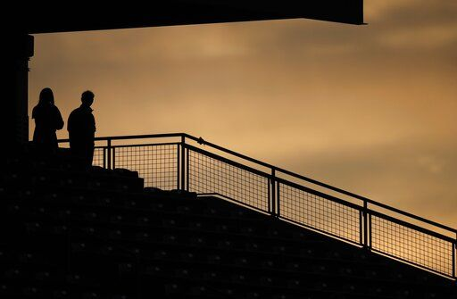 Two fans are silhouetted against the sky near sunset, during the fourth inning of a baseball game between the San Diego Padres and the Colorado Rockies on Friday, May 10, 2019, in Denver.