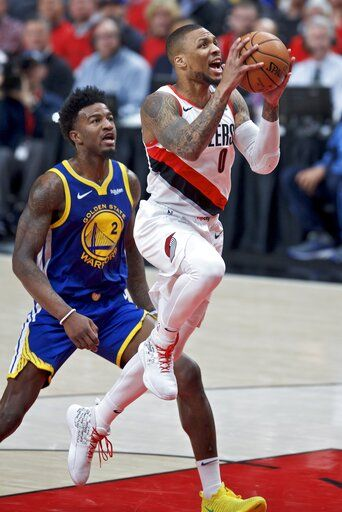 Portland Trail Blazers guard Damian Lillard, right, shoots past Golden State Warriors forward Jordan Bell during the first half of Game 4 of the NBA basketball playoffs Western Conference finals Monday, May 20, 2019, in Portland, Ore.