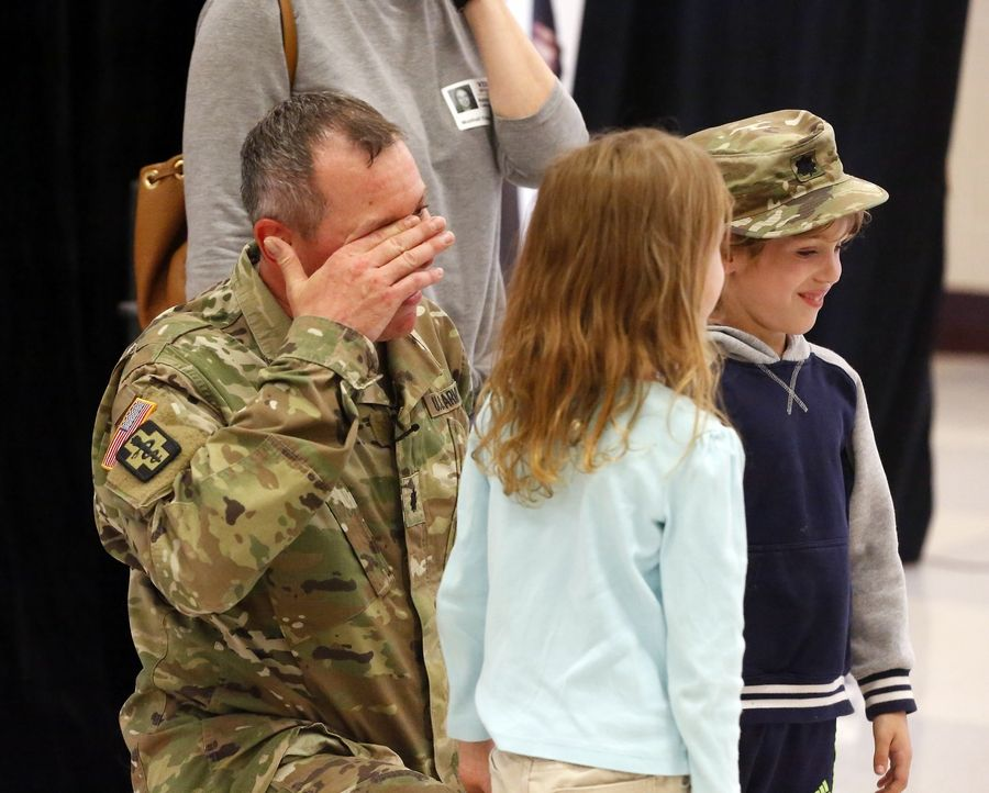 Lt. Col. Robert Gerlach of St. Charles wipes a tear away after he was reunited with his 6-year-old children Colin and Ava at Munhall Elementary School, Friday in St. Charles.