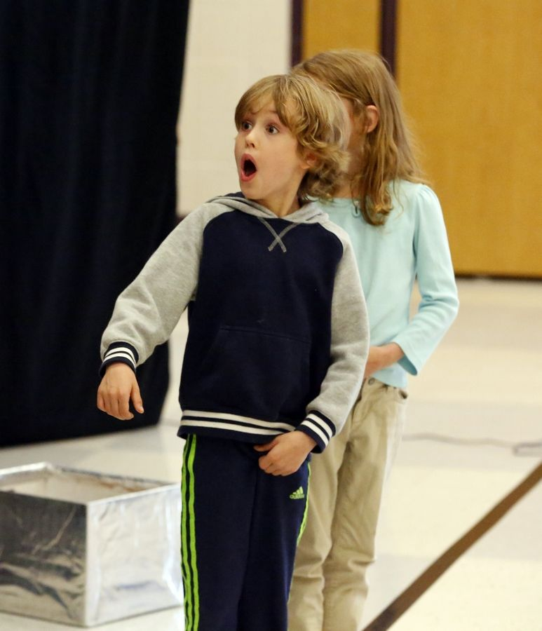 Six-year-old Colin Gerlach and his sister, Ava, react Friday at Munhall Elementary School in St. Charles, as they see their dad for the first time since July. Lt. Col. Robert Gerlach of St. Charles, who has been deployed to Kuwait, surprised the youngsters during a magic show.