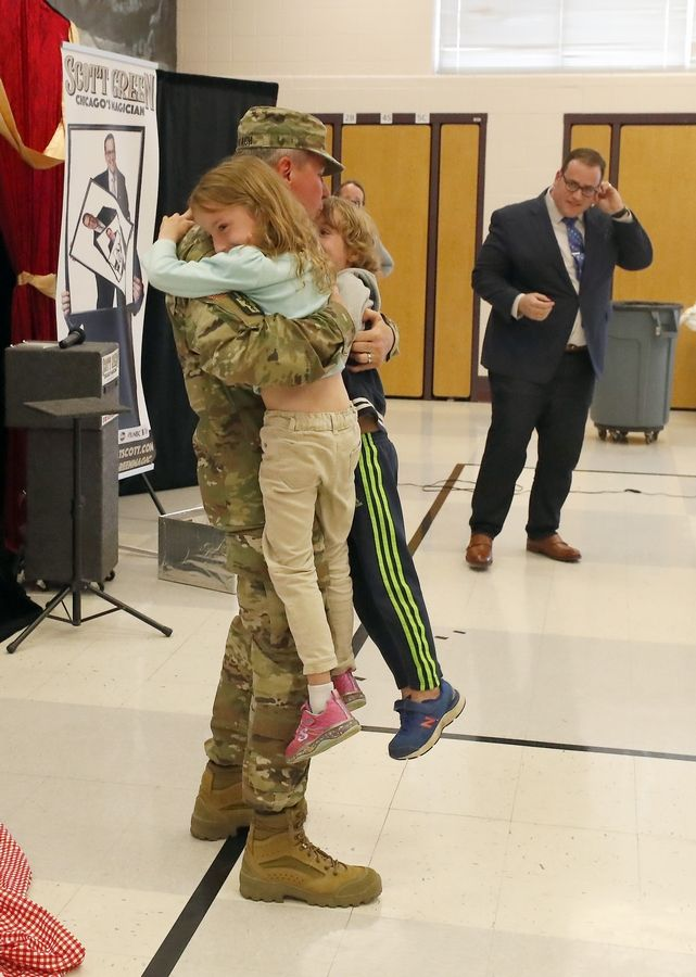 St. Charles resident Lt. Col. Robert Gerlach gets a giant hug from his children Colin and Ava, both 6, Friday at Munhall Elementary School, in St. Charles. Magician Scott Green, right, made Gerlach appear in a trick before the two and their schoolmates.