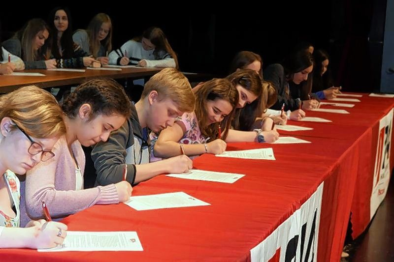 Students sign letters of intent to become teachers at District 214's Educator Prep signing ceremony.