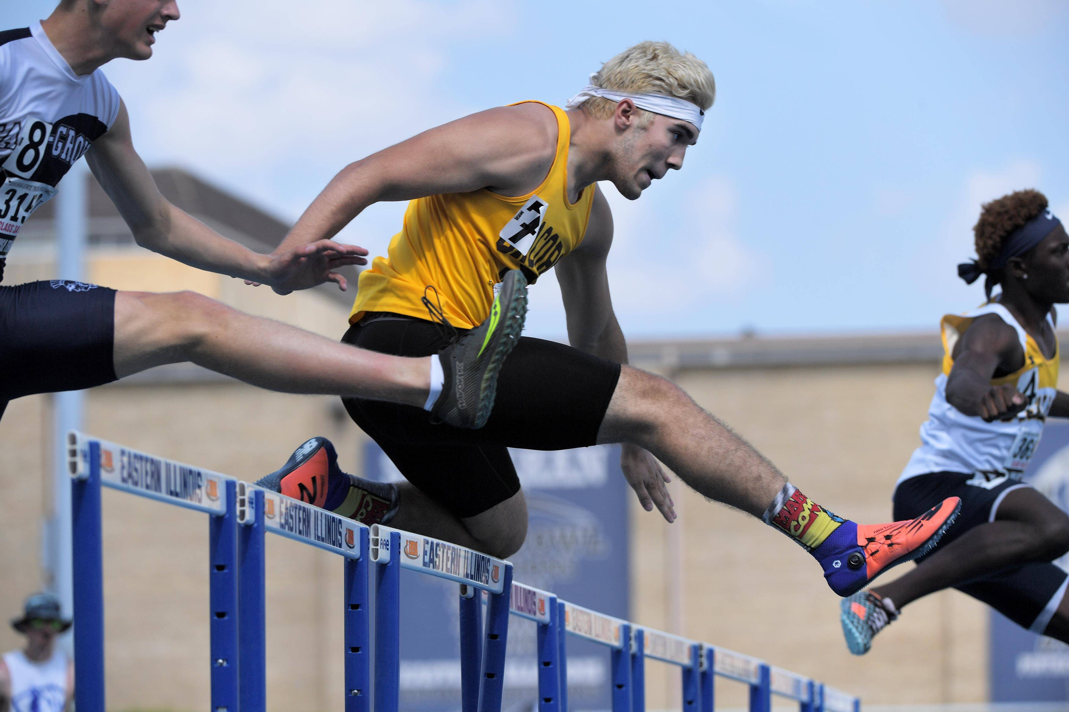 Jacobs' Tommy Subaric clears a hurdle in the Class 3A 300-meter hurdles at the IHSA boys state track preliminary events in Charleston Friday.