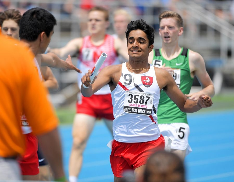 Mundelein's Aidan Afonso hands the stick to teammate Dario Carrillo in the Class 3A 3,200-meter relay at the IHSA boys state track preliminary events in Charleston Friday.