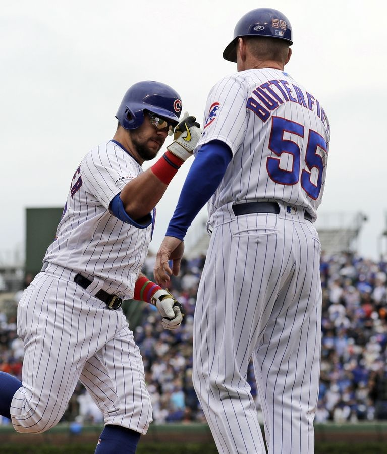 The Cubs' Kyle Schwarber is congratulated by third base coach Brian Butterfield after belting a solo homer in the first inning of Friday's 6-5 loss to Cincinnati at Wrigley Field.