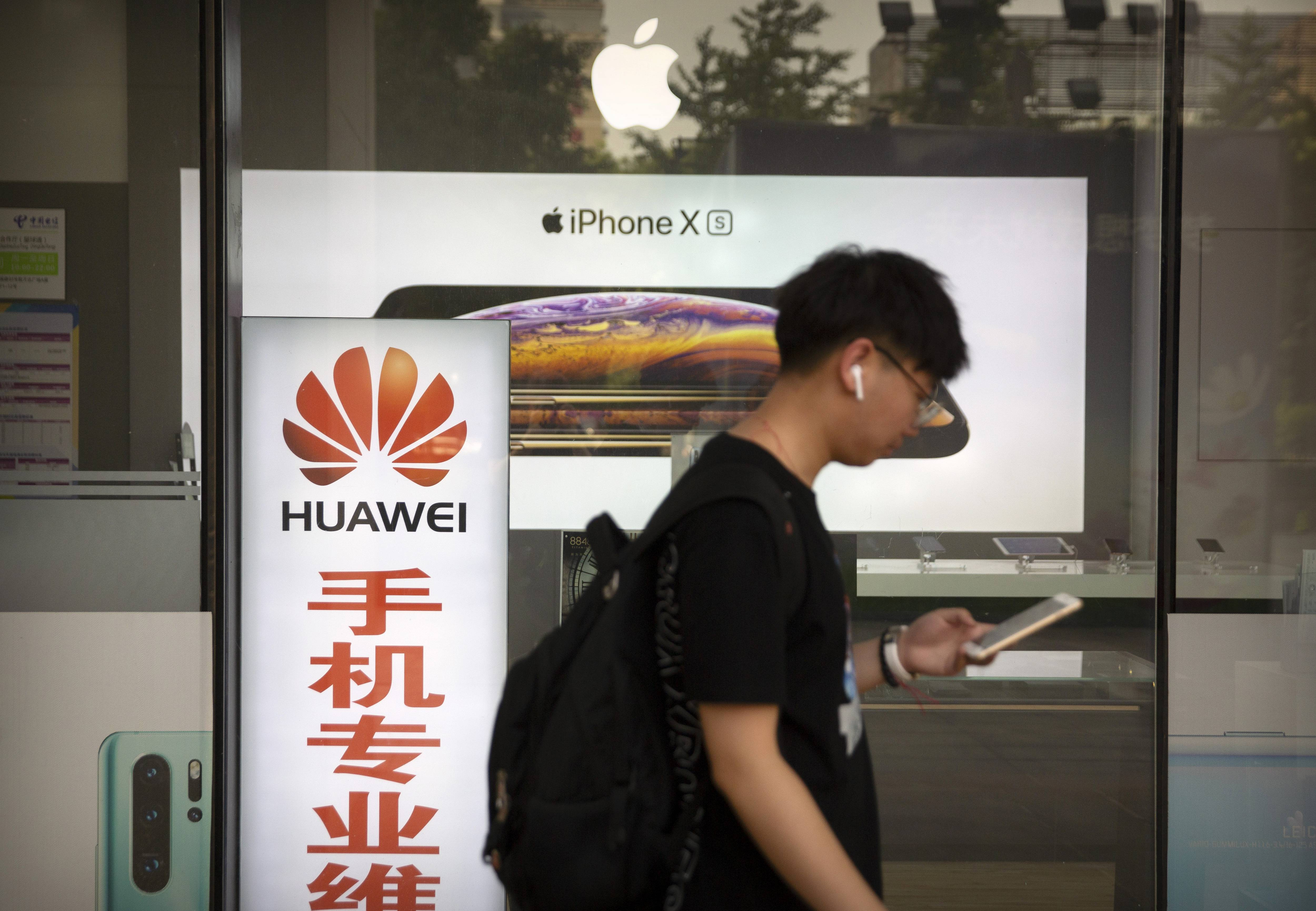 "A man looks at his smartphone Friday as he walks past an electronics shop advertising phones from Huawei and Apple in Beijing. Stepping up a propaganda offensive against Washington, China's state media on Friday accused the U.S. of seeking to ""colonize global business"" by targeting telecom equipment giant Huawei and other Chinese companies."