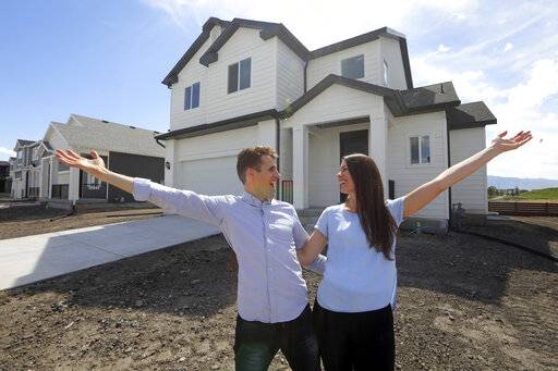 ADVANCE FOR RELEASE SATURDAY MAY 25, 2019, AND THEREAFTER - In this April 27, 2019, photo, Andy and Stacie Proctor stand in front of their new home in Vineyard, Utah. For some millennials looking to buy their first home, the hunt feels like a race against the clock. The Proctors ultimately made a successful offer on a three-bedroom house for $438,000 in Vineyard. (AP Photo/Rick Bowmer)