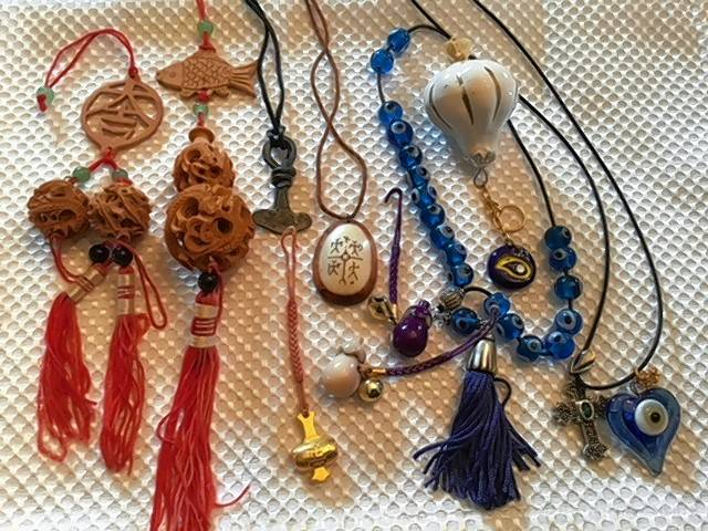 I have collected charms from all over — China with red tassels;, white reindeer horn with symbol from Lapland; Thor's hammer from Sweden; and others —each brings its own luck or protection.