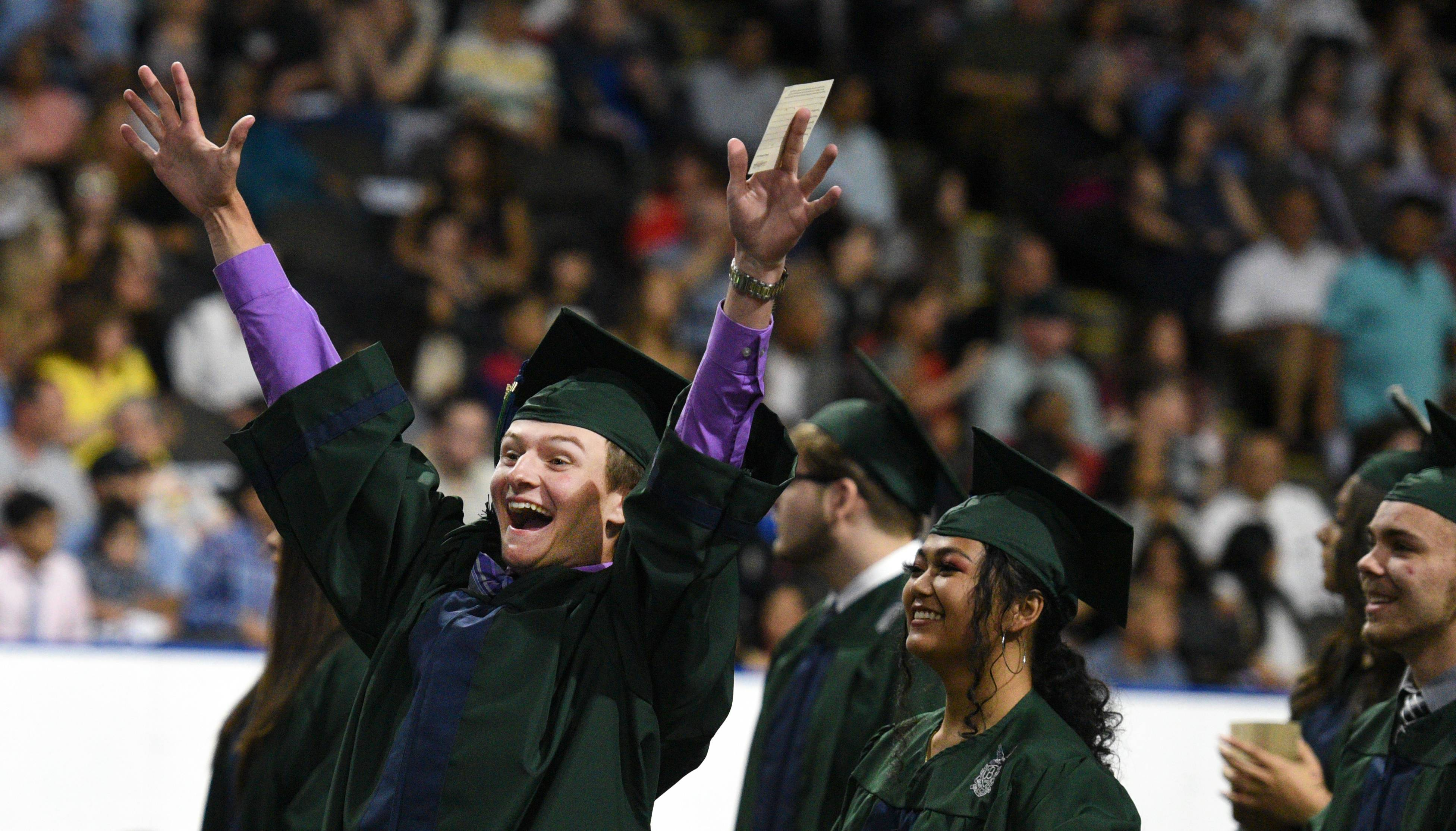 Justin Everson throws his arms up to acknowledge voices yelling at him from the crowd as the graduates process during the Bartlett High School graduation at the Sears Centre in Hoffman Estates on Saturday.