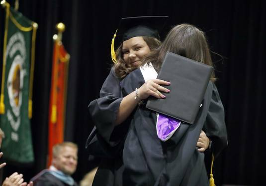 Graduate Caroline Ripp, left, gets a big hug from English Department Teacher Megan Davis Saturday during Wheaton Warrenville South High School graduation at College of DuPage in Glen Ellyn.