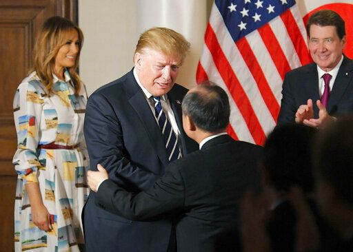 U.S. President Donald Trump, center left, greets SoftBank Group Corp.'s Chief Executive Masayoshi Son, center right,  as first lady Melania Trump, left, and U.S. Ambassador to Japan William Hagerty looks on during his meeting with business leaders, in Tokyo, Saturday, May 25, 2019.  President Trump is on a four-day state visit in Japan. (Kyodo News via AP)