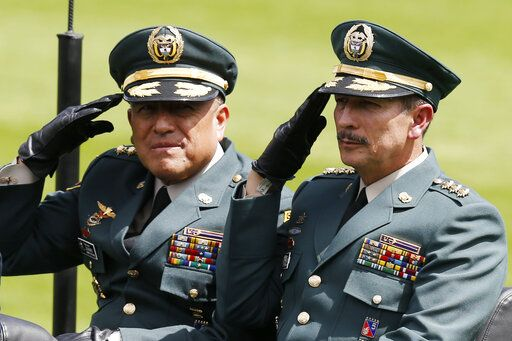 FILE - In this Dec. 17, 2018 file photo, Army Commander Gen. Nicacio Martinez Espinel, right, salutes during a swearing-in ceremony for the new military and police commanders, in Bogota, Colombia. New evidence has emerged linking Martinez Espinel to the alleged cover up of civilian killings more than a decade ago. The documents, provided to The Associated Press by a person familiar with an ongoing investigation into the extrajudicial killings, come as Martinez Espinel faces mounting pressure to resign over orders he gave troops this year, 2019, to step up attacks in what some fear could pave the way for a return of serious human rights violations.