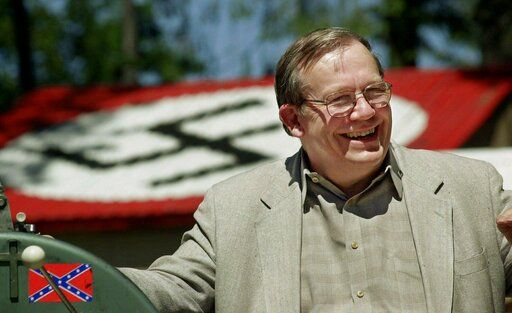 FILE - In this May 22, 2001, file photo, Norm Gissel smiles as he talks about the imminent dismantling of the former headquarters of the Aryan Nations in Hayden Lake, Idaho. Behind Gisel is a Nazi insignia painted atop the roof of the compound's cafeteria. Nearly two decades after the Aryan Nations compound was demolished in Idaho, far-right extremists are maintaining a presence in the Pacific Northwest.