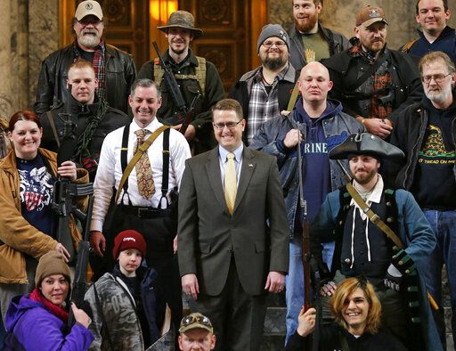"FILE - In this Jan. 15, 2015, file photo, Washington Rep. Matt Shea, R-Spokane Valley, center, poses for a group photo with gun owners inside the Capitol in Olympia, Wash., following a gun-rights rally. Recently published internet chats from 2017 show Shea and three other men discussing confronting ""leftists"" with a variety of tactics, including violence, surveillance and intimidation. The messages prompted Washington House Democrats to demand that Shea be reprimanded for a history of far-right speech and activities."