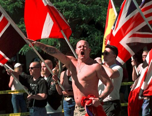 FILE - In this July 18, 1998, file photo, Karl Wolf raises his arm in a Nazi salute as he marches through the streets of Coeur d'Alene, Idaho, where scores of police in riot gear stood between parading white supremacists and protesters who jeered at the Aryan Nations marchers. Nearly two decades after the Aryan Nations compound was demolished in Idaho, far-right extremists are maintaining a presence in the Pacific Northwest. White nationalism has been on the rise across the U.S., but it has particular resonance along the Idaho-Washington border.