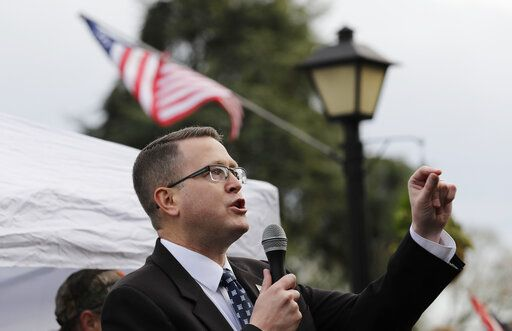 "FILE - In this Jan. 18, 2019, file photo, Rep. Matt Shea, R-Spokane Valley, speaks at a gun-rights rally at the Capitol in Olympia, Wash. Recently published internet chats from 2017 show Shea and three other men discussing confronting ""leftists"" with a variety of tactics, including violence, surveillance and intimidation. The messages prompted Washington House Democrats to demand that Shea be reprimanded for a history of far-right speech and activities."