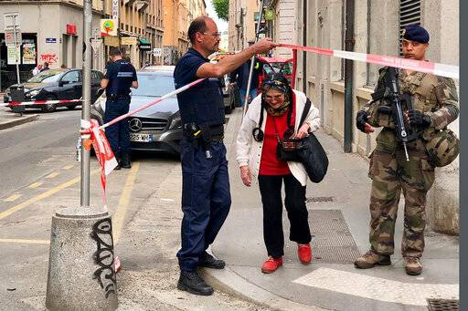 A police officer lets an elderly woman leaving the area while soldiers secure the access near the site of a suspected bomb attack in central Lyon, Friday May, 24, 2019. An explosion Friday on a busy pedestrian street in the French city of Lyon injured seven people, local officials said. (AP Photo/Sebastien Erome)