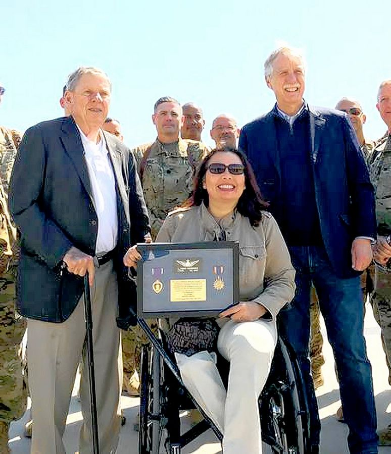 During a bipartisan congressional delegation visit to Iraq in April, Republican U.S. Sen. Johnny Isakson of Georgia, left, presents Democratic U.S. Sen. Tammy Duckworth of Hoffman Estates with a plaque commemorating her military service there. At right is U.S. Sen. Angus King of Maine.