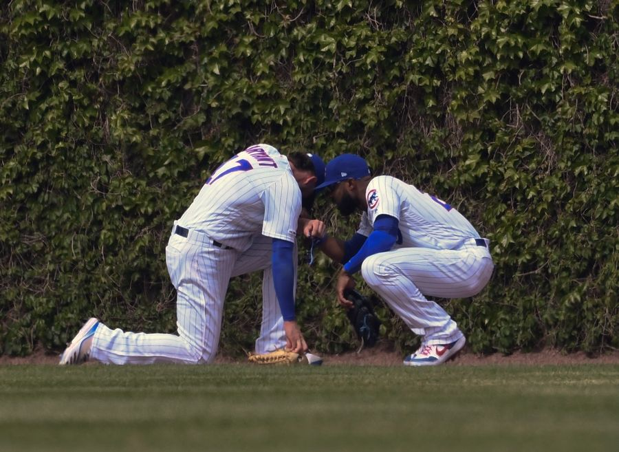 Chicago Cubs center fielder Jason Heyward, right, and right fielder Kris Bryant (17) take a moment after colliding while chasing a ball hit by Cincinnati Reds' Eugenio Suarez (7) during the sixth inning of a baseball game Sunday, May 26, 2019, in Chicago. Bryant was charged with an error on the play.