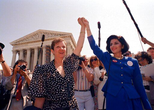 FILE - In this Wednesday, April 26, 1989 file photo, Norma McCorvey, Jane Roe in the 1973 court case, left, and her attorney Gloria Allred hold hands as they leave the Supreme Court building in Washington after sitting in while the court listened to arguments in a Missouri abortion case. A wave of state abortion bans in 2019 has set off speculation: What would happen if Roe v. Wade, the ruling establishing abortion rights nationwide, were overturned?