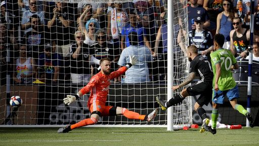 Sporting Kansas City forward Johnny Russell (7) gets the ball past Seattle Sounders goalkeeper Stefan Frei, left, to score a goal during the first half of an MLS soccer match Sunday, May 26, 2019, in Kansas City, Kan.