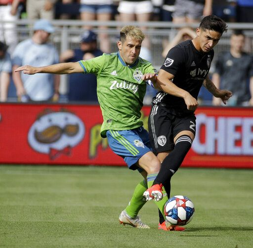 Seattle Sounders midfielder Nicolas Lodeiro, left, and Sporting Kansas City midfielder Felipe Gutierrez battle for the ball during the first half of an MLS soccer match Sunday, May 26, 2019, in Kansas City, Kan.