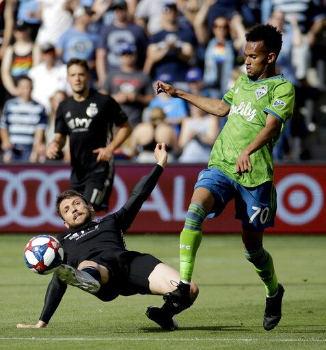 Sporting Kansas City midfielder Ilie Sanchez kicks the ball away from Seattle Sounders forward Handwalla Bwana (70) during the first half of an MLS soccer match Sunday, May 26, 2019, in Kansas City, Kan.
