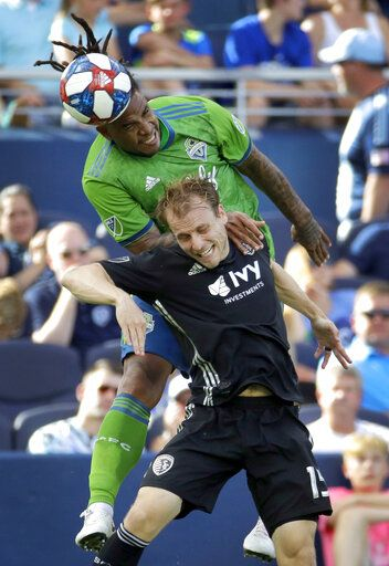 Seattle Sounders defender Roman Torres, top, and Sporting Kansas City defender Seth Sinovic battle for control of the ball during the first half of an MLS soccer match Sunday, May 26, 2019, in Kansas City, Kan.