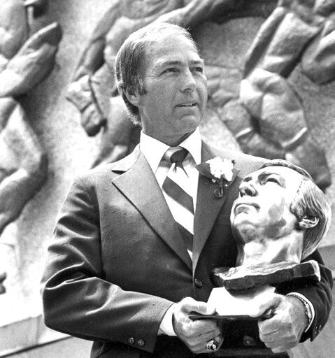 FILE - In this July 30, 1977, file photo, Bart Starr poses with his bust after his induction into the Pro Football Hall of Fame in Canton, Ohio.  Starr, the Green Bay Packers quarterback and catalyst of Vince Lombardi's powerhouse teams of the 1960s, has died. He was 85. The Packers announced Sunday, May 26, 2019, that Starr had died, citing his family. He had been in failing health since suffering a serious stroke in 2014.