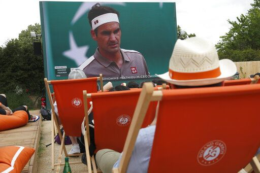 Spectators in lounge chairs watch Roger Federer, on screen, rear, play Italy's Lorenzo Sonego during their first round match of the French Open tennis tournament at the Roland Garros stadium in Paris, Sunday, May 26, 2019.