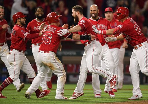 Los Angeles Angels' Jared Walsh, center right, celebrates with Kole Calhoun, center left, after Walsh hit a walk-off single during the ninth inning of the team's baseball game against the Texas Rangers on Saturday, May 25, 2019, in Anaheim, Calif. The Angels won 3-2.