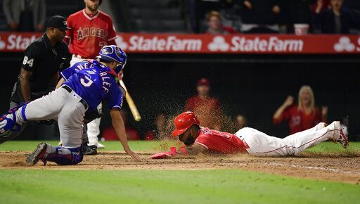 Los Angeles Angels' Luis Rengifo, right, scores on a double by Kole Calhoun as Texas Rangers catcher Isiah Kiner-Falefa reaches for a late tag during the ninth inning of a baseball game Saturday, May 25, 2019, in Anaheim, Calif.