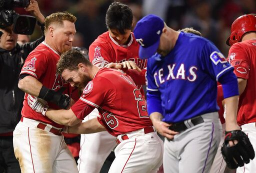 Los Angeles Angels' Jared Walsh, second from left, celebrates with Kole Calhoun, left, and Shohei Ohtani, center, of Japan, after Walsh hit a walk-off single. as Texas Rangers relief pitcher Shawn Kelley walks off the field at the end of the baseball game Saturday, May 25, 2019, in Anaheim, Calif. The Angels won 3-2.