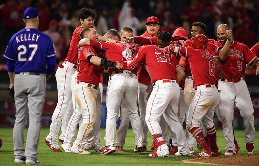 Los Angeles Angels celebrate after Jared Walsh, fourth from left, hit a walk-off single to score Kole Calhoun, to his left, as Texas Rangers relief pitcher Shawn Kelley watches at the end of a baseball game Saturday, May 25, 2019, in Anaheim, Calif. The Angels won 3-2.