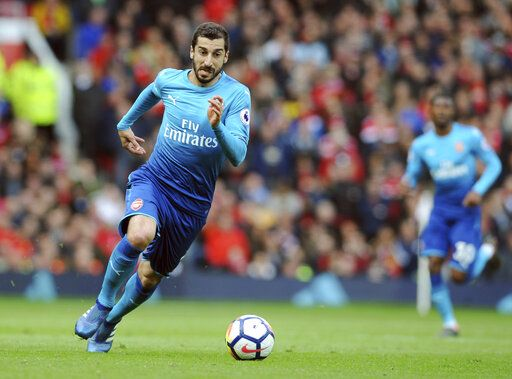 "FILE - In this Sunday, April 29, 2018 file photo, Arsenal's Henrikh Mkhitaryan runs with the ball during their English Premier League soccer match against Manchester United at the Old Trafford stadium in Manchester, England. Arsenal's Granit Xhaka and Sokratis Papastathopoulos say they want to win the Europa League title for their teammate Henrikh Mkhitaryan, who is missing the final on Wednesday, May 29, 2019 for political reasons. Xhaka says ""of course we're disappointed he's not here,� adding that ""we want to give him a trophy too.�"