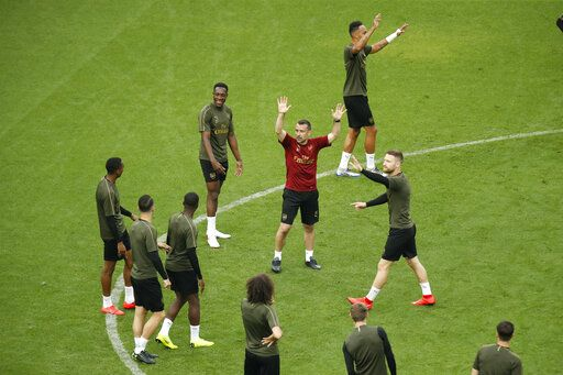 Arsenal players including Pierre-Emerick Aubameyang, top right, Danny Welbeck, fourth left, and Shkodran Mustafi, right, take part in a soccer training session at the Olympic stadium in Baku, Azerbaijan, Tuesday, May 28, 2019. English Premier League teams Arsenal and Chelsea are preparing for the Europa League Final soccer match that takes place in Baku on Wednesday night.