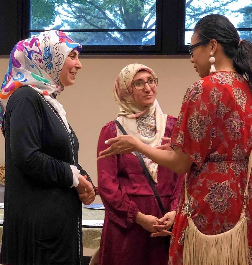 Donna Marie Post, right, founder of women's empowerment organization, I Admire You, discusses future engagement ideas with Ikbal Koseli, left, outreach coordinator from Turkish American Society and Nesrin Unlu, middle, from the Islamic Society of Midwest, both based in Mount Prospect.
